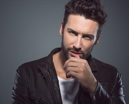 Hombre seductor fresco en negro coqueteo chaqueta de cuero y mirando a la cámara