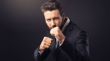 aggressive people: Angry aggressive businessman showing fists and ready to attack Stock Photo
