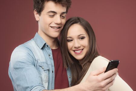 couple talking: Young teen couple having fun together with a smart phone