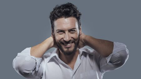 man style: Cheerful smiling man relaxing with hands behind head