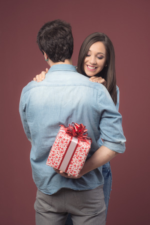 receiving: Smiling young woman receiving a beautiful gift with red ribbon from her boyfriend