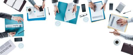 Equipo de negocios de encuentro y trabajo en el escritorio de la oficina, las manos vista desde arriba, la gente irreconocibles, espacio de la copia en blanco