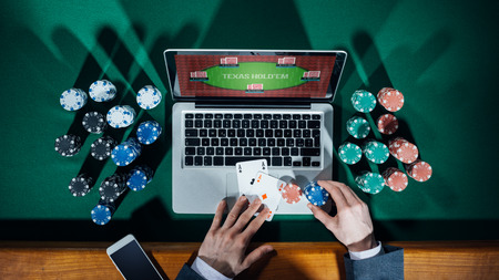 Man playing online poker with laptop on a green table with chips all around, top view