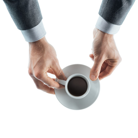 holding close: Professional businessman having a coffee break and holding a cup with espresso on white background, top view hands close up