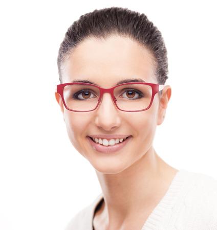 chicas sonriendo: Modelo de manera sonriente joven posando sobre fondo blanco con elegantes gafas de color rojo