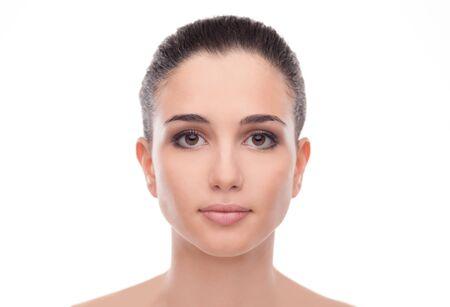 Mujer joven atractiva con piel de la cara brillante sonriente y posando sobre fondo blanco Foto de archivo