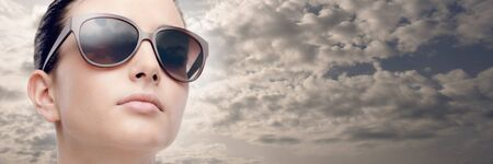 flawless: Young female fashion model wearing big sunglasses, cloudy sky on background