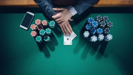 poker player: Elegant male poker player with smartphone holding two aces with stacks of chips all around, hands detail top view