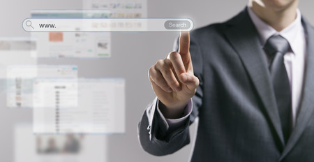 Businessman using a search engine and pressing a search button with web pages on background Stock Photo