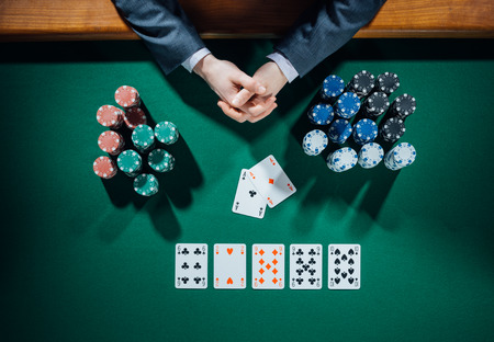 Poker player's hands with cards and stacks of chips all around on green table, top view