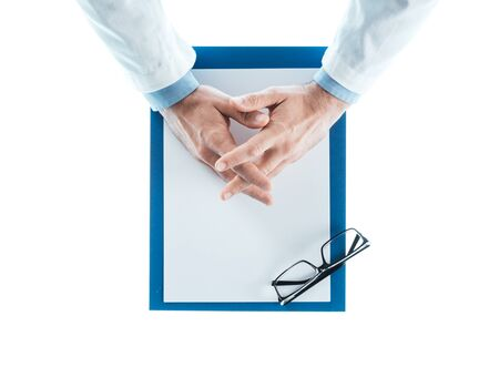 medical exam: Doctor with hands clasped waiting at desk on white background, top view, healthcare and prevention concept