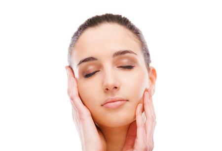 limpieza de cutis: Mujer hermosa joven tocando la piel de la cara radiante con los ojos cerrados sobre fondo blanco