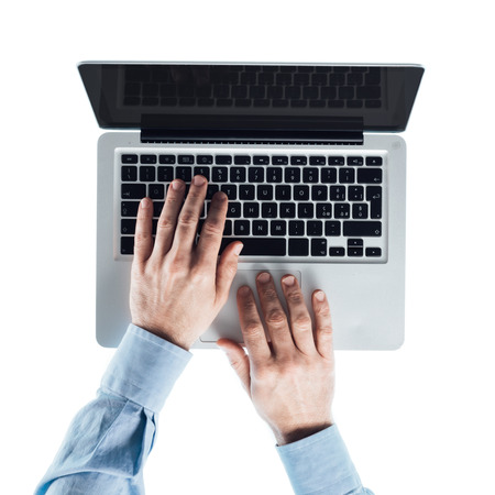 computer desk: Businessman working at computer and typing on a laptop keyboard, top view, hands close up Stock Photo