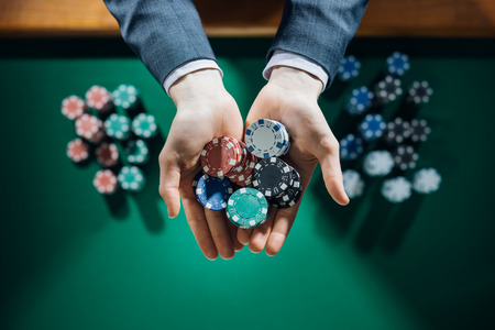 fichas de casino: Elegante jugador de casino masculino que sostiene un pu�ado de patatas fritas con el cuadro verde en el fondo, las manos se cierran encima de la vista superior Foto de archivo