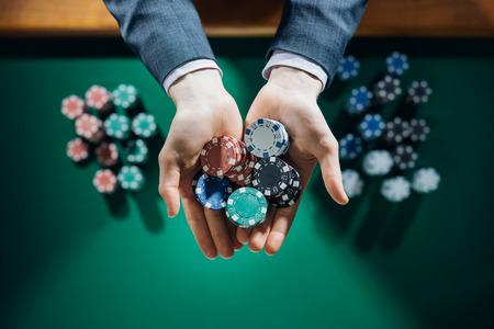 Joueur de casino masculine élégante tenant une poignée de copeaux avec table verte sur fond, les mains se referment vue de dessus