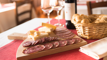 table set: Tasty appetizers at restaurant, salami and cheese on a wooden cutting board with bread and wine