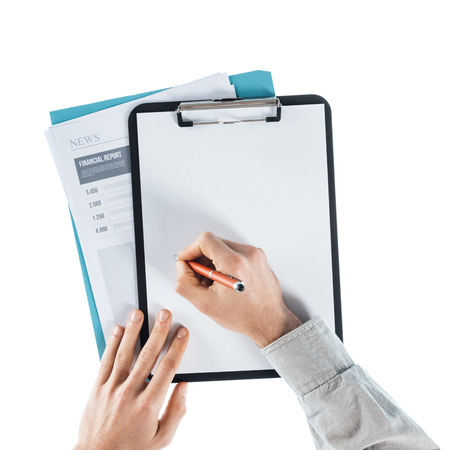 man writing: Businessman writing down notes on a  blank clipboard and financial reports, hands close up, top view Stock Photo