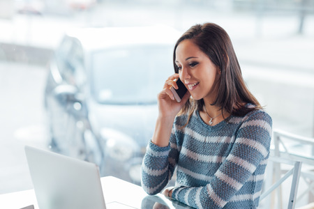 Beautiful young girl having a phone call sitting next to a window Stock Photo