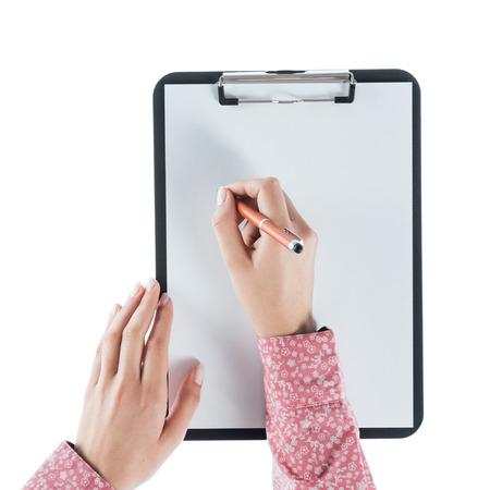 papeles oficina: Mujer joven a escribir en una tablilla sobre una hoja en blanco sobre fondo blanco, las manos se cierran para arriba Foto de archivo