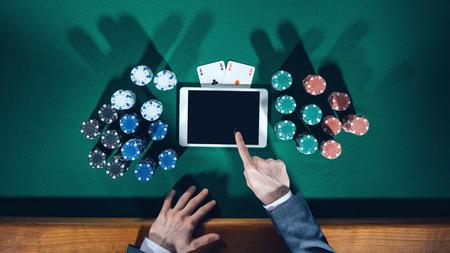 les mains de joueur de poker avec tablette numérique, piles de jetons et les cartes sur table verte, vue de dessus Banque d'images
