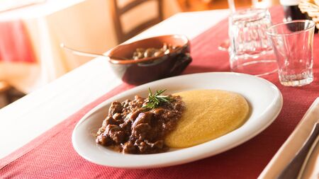 polenta: Tasty italian lunch at the restaurant: polenta with deer stew Stock Photo