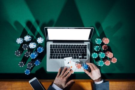 fichas casino: Hombre que juega el póker en línea con el ordenador portátil sobre una mesa verde con chips de todo, la vista superior