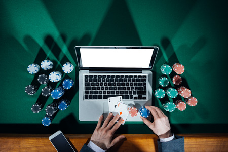 cards poker: Man playing online poker with laptop on a green table with chips all around, top view