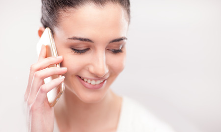 pretty young woman: Pretty young woman having a phone call with her mobile on white background Stock Photo