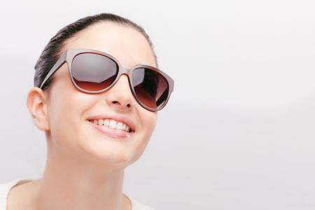 jovem: Modelo de forma fêmea novo que desgasta grandes óculos de sol sorrindo