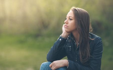 mujer pensativa: mujer pensativa joven que se relaja en el parque sentado en la hierba Foto de archivo