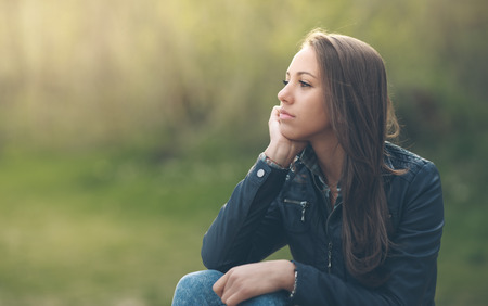 sit: Young pensive woman relaxing at the park and sitting on grass