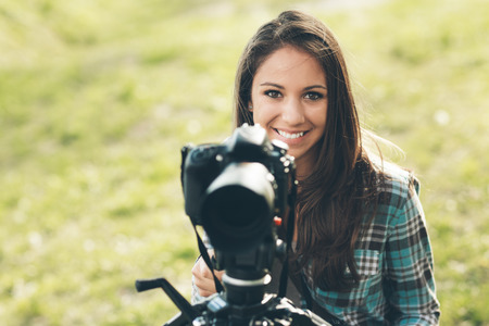 Smiling female photographer using a professional digital camera on a tripod, natural landscape on background