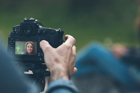 クローズ アップの写真撮影手と背景にポーズをとるモデル