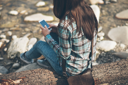 river trunk: Young woman sitting along the river on a wooden trunk and texting with her mobile phone