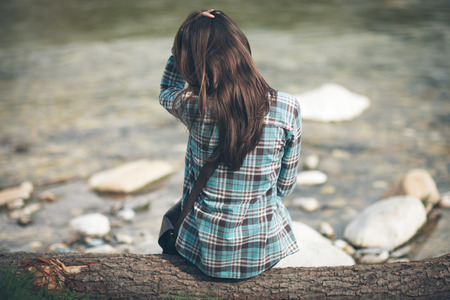Young woman sitting along the river, relaxing and looking away Stock Photo