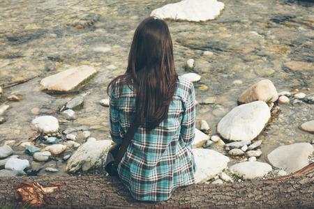 persona sentada: Mujer joven que se sienta a lo largo del río, se relaja y que mira lejos