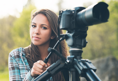 camera girl: Young female photographer and videomaker shooting in a green natural setting with grass on background