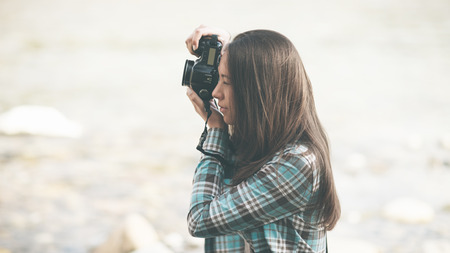 camera girl: Young female photographer shooting, natural landscape on background