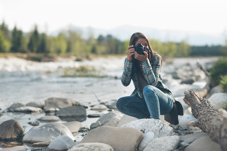 female photographer: Young female photographer shooting, natural landscape on background