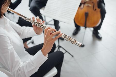 musica clasica: Femenina Profesional flustist tocando su instrumento en el escenario con la m�sica cl�sica orquesta sinf�nica Foto de archivo