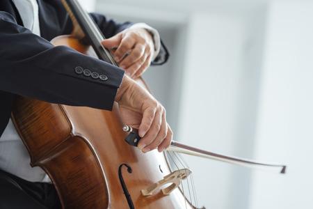 Cello profesional rendimiento del jugador en solitario la música clásica, las manos cerca, persona irreconocible