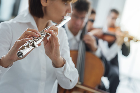 rehearsal: Professional female flustist playing her instrument on stage with classical music symphony orchestra