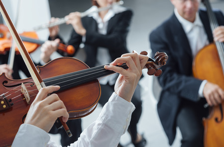 classical music: Classical music symphony orchestra string section performing, female violinist playing on foreground, hands close up Stockfoto