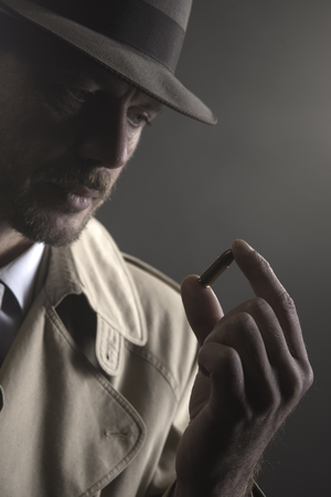 Handsome pensive detective holding a bullet, film noir Stock Photo