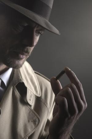 film noir: Handsome pensive detective holding a bullet, film noir Stock Photo