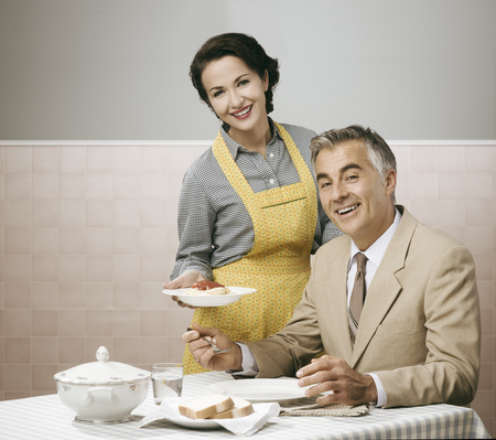 servings: Vintage smiling woman serving pasta for lunch to her happy husband Stock Photo