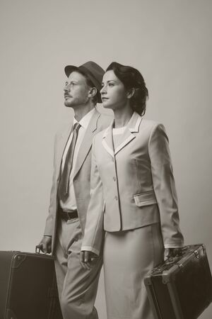 vintage travel: Elegant vintage couple walking and holding suitcases, travel concept