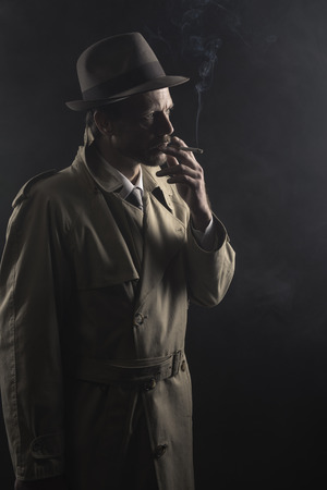 mafia: 1950s style agent smoking a cigarette at night and looking away, film noir