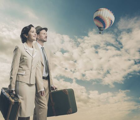 married couples: Elegant vintage couple walking and holding suitcases, sky and hot air balloon on background Stock Photo