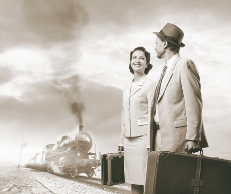 steam train: Elegant vintage couple walking and holding suitcases with steam train on background, travel concept